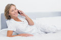 Happy blonde woman lying on bed making a phone call Royalty Free Stock Photo