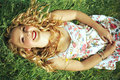 Happy blonde woman lying on grass smiling with long curly hair and red lips wearing a white flower print summer dress is down the Royalty Free Stock Image