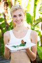 Happy blonde woman presenting plate with herbal medicine Royalty Free Stock Photo