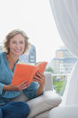 Happy blonde woman sitting on her couch holding a book smiling at camera at home in the room Royalty Free Stock Photos