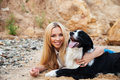 Happy blonde young woman hugging her dog on the beach Royalty Free Stock Photo