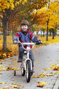 Happy boy in autumn park rides his bike Stock Photo
