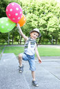 Happy boy with balloons funny little playing in a green summer park Royalty Free Stock Photos