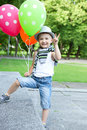 Happy boy with balloons funny little playing in a green summer park Stock Images