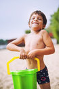 Happy boy on beach carrying a bucket of sand Royalty Free Stock Photography