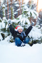 Happy boy in a cap of Santa Claus in the winter forest. Royalty Free Stock Photo
