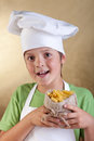 Happy boy with chef hat holding raw pasta in small sack Stock Photos