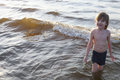 Happy boy coming out of the sea after swimming caucasian standing knee deep in and smiling Royalty Free Stock Photography