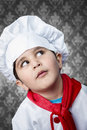 Happy boy cook in uniform over vintage background funny look cooking Royalty Free Stock Image