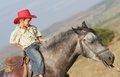 Happy boy in cowboy hat riding horse outdoors Royalty Free Stock Images
