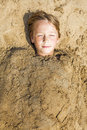 Happy boy dig oneself in the sand at beach and has fun Royalty Free Stock Images