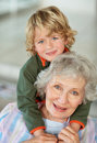 Happy boy embracing his grandmother from back Royalty Free Stock Images