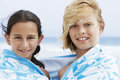 Happy boy and girl wrapped in towel together at beach portrait of cute little preadolescent Royalty Free Stock Photo