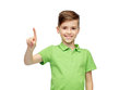 Happy boy in green polo t-shirt pointing finger up