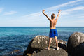 Happy boy with hands raised standing on a rock by the sea Royalty Free Stock Images