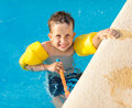 Happy boy having a fun at swimming pool with water wings and snorkel Stock Photo
