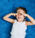 Happy boy hiding kid on blue carpet in living room at home Stock Photo