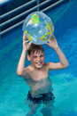 Happy boy hold inflatable globe  in pool Royalty Free Stock Photos