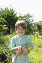 Happy boy holding marrow in garden portrait of young community Royalty Free Stock Photography