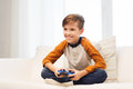 Happy boy with joystick playing video game at home