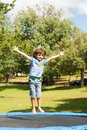 Happy boy jumping high on trampoline  in the park Stock Images