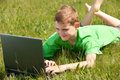 Happy boy with laptop on the grass Royalty Free Stock Photo