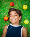 Happy boy listening to music portrait of a cute smiling teen lying down on a fresh green grass field summer weekend Royalty Free Stock Photography