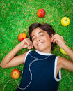 Happy boy listening to music portrait of a cute smiling teen lying down on a fresh green grass field summer weekend Stock Photography