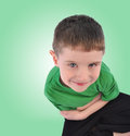 Happy boy looking up on green background a young child is sitting down an with copyspace the is thinking Stock Photo