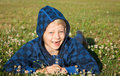 Happy boy lying in grass smiling a cute with clover with missing front teeth Royalty Free Stock Photo