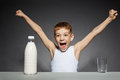 Happy boy opening bottle of milk over grey background Stock Photos