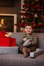 Happy boy opening christmas presents portrait of little sitting on couch smiling Royalty Free Stock Image