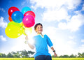 Happy Boy Outdoors With A Dozen Of Helium Balloons Royalty Free Stock Photo