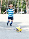 Happy boy playing football outdoor Stock Photo