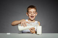 Happy boy pouring milk into glass over grey background Royalty Free Stock Photo