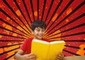 Happy boy reading against red, black and orange splattered background Royalty Free Stock Photo