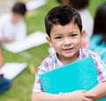 Happy boy at the school holding a notebook and smiling Stock Photo