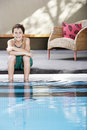 Happy boy sitting on the edge of swimming pool portrait smiling teenage with legs in water Stock Photos