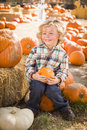 Happy boy sitting and holding his pumpkin at pumpkin patch adorable little in a rustic ranch setting the Royalty Free Stock Images