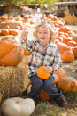 Happy boy sitting and holding his pumpkin at pumpkin patch adorable little in a rustic ranch setting the Stock Image