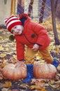Happy boy sitting on pumpkin outdoors in autumn. Helloween. Royalty Free Stock Photo