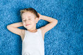 Happy boy smiling kid eyes closed blue carpet living room home Stock Photos