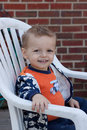 Happy boy smiling toddler sitting in a white chair Stock Photography