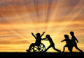 Happy boy in wheelchair playing with children sunset Royalty Free Stock Photo