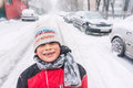 Happy boy in winter standing on snow covered street Royalty Free Stock Images