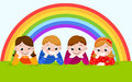 Happy boys and girls lying on a green grass with rainbow Royalty Free Stock Photo