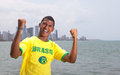 Happy brazilian guy at beach soccer fan from brasil cheering with skyline in the background Stock Photo