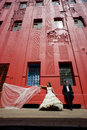 Happy bridal couple standing on sidewalk below tall red building Royalty Free Stock Photo