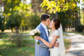 Happy bride, groom dancing in green park, kissing, smiling, laughing. lovers in wedding day. happy young couple in love. Royalty Free Stock Photo