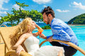 Happy bride and groom enjoy a cocktail poolside infinity tropic tropical sea in the background Royalty Free Stock Image